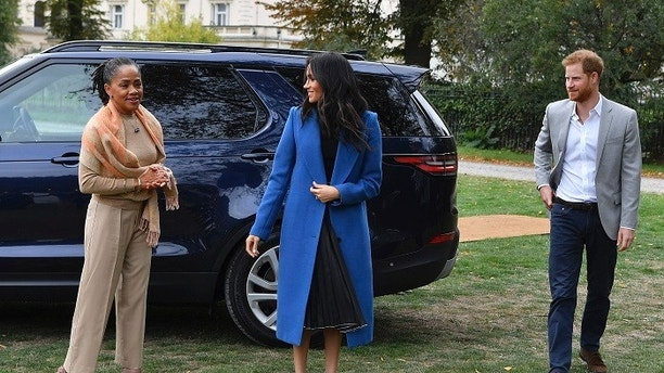"""Meghan, the Duchess of Sussex, centre, accompanied by Britain's Prince Harry, the Duke of Sussex and her mother Doria Ragland walk to attend a reception at Kensington Palace, in London, Thursday Sept. 20, 2018.  Markle was joined by her mother for the launch of a cookbook aimed at raising money for victims of the Grenfell fire. Markle, now the Duchess of Sussex, hosted the reception beside her mother, Doria Ragland, to support the cookbook called """"Together."""" (Ben Stansall/Pool Photo via AP)"""