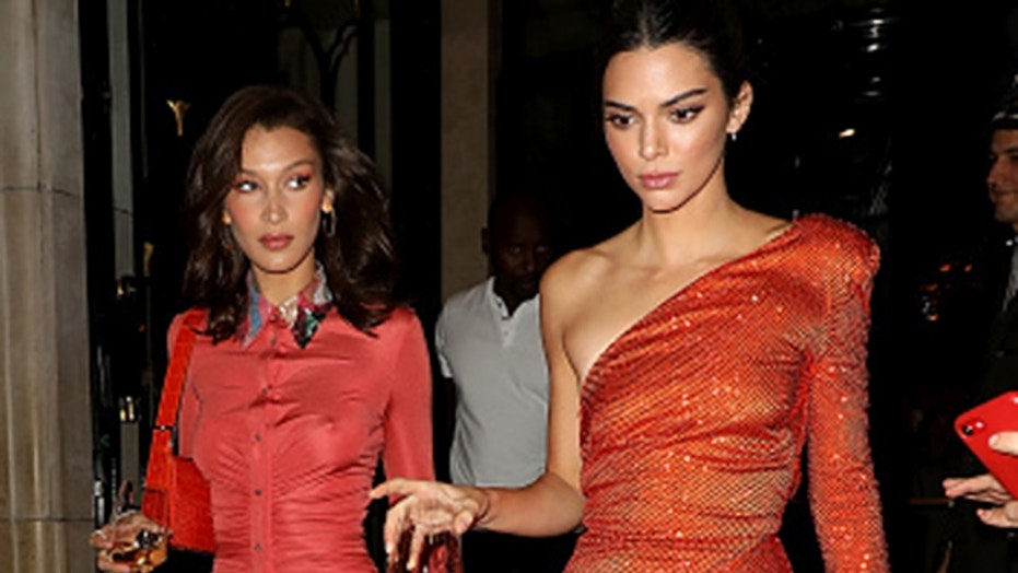 Supermodels Bella Hadid and Kendall Jenner leave a hotel on September 26, 2018 in Paris, France with wine glasses.