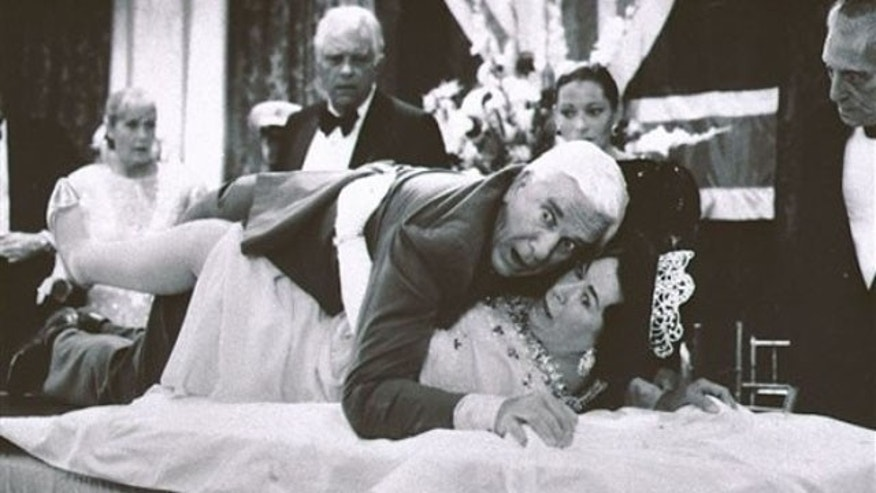 "FILE - This 1988 publicity file photo provided by Paramount Pictures shows actor Leslie Nielsen, center top, with actress Jeannette Charles,  portraying the Queen of England, in a scene from ""The Naked Gun"". The Canadian-born Nielsen, who went from drama to inspired bumbling as a hapless doctor in ""Airplane!"" and the accident-prone detective Frank Drebin in ""The Naked Gun"" comedies, has died. He was 84. His agent John S. Kelly said Nielsen died Sunday, Nov. 28, 2010, at a hospital near his home in Florida where he was being treated for pneumonia. (AP Photo/Paramount Pictures, Elliott Marks, File)"