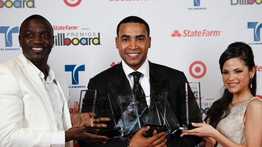 Singer Don Omar, center, gets helps in holding his eight awards from singer Akon, left, and an unidentified woman during the Latin Billboard Awards in Coral Gables, Fla. Thursday, April 26, 2012.  (AP Photo/Wilfredo Lee)