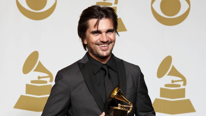 "Juanes poses backstage with the award for best Latin pop album for ""MTV Unplugged Deluxe Edition"" at the 55th annual Grammy Awards on Sunday, Feb. 10, 2013, in Los Angeles. (Photo by Matt Sayles/Invision/AP)"