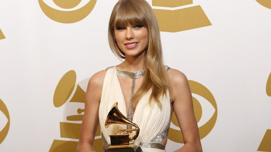 "Taylor Swift holds the award for Best Song Written For Visual Media for ""Safe & Sound"" backstage at the 55th annual Grammy Awards in Los Angeles, California February 10, 2013.  REUTERS/Mario Anzuoni (UNITED STATES  - Tags: ENTERTAINMENT)  (GRAMMYS-BACKSTAGE)"
