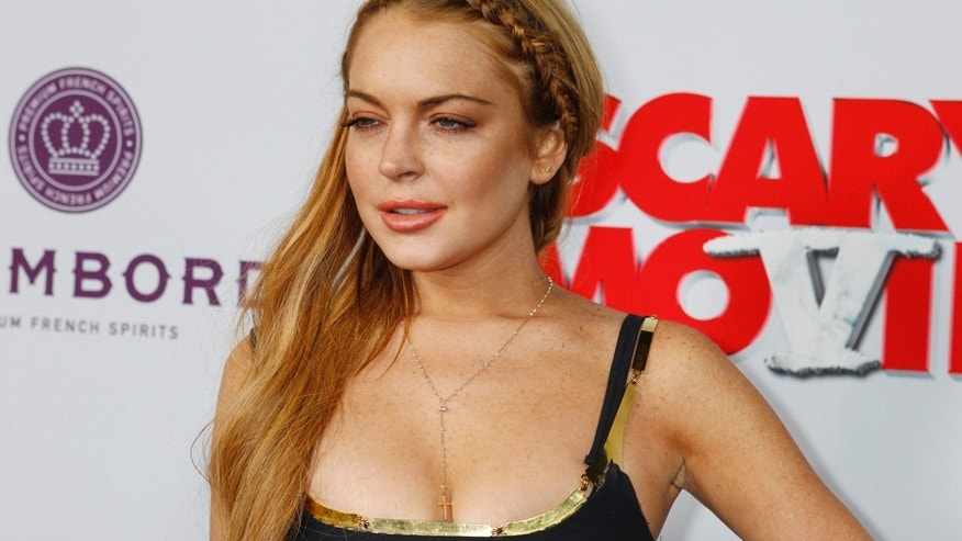 "Actress Lindsay Lohan arrives at the premiere of the film ""Scary Movie 5"" in Hollywood April 11, 2013. REUTERS/Fred Prouser (UNITED STATES - Tags: ENTERTAINMENT) - RTXYIKG"