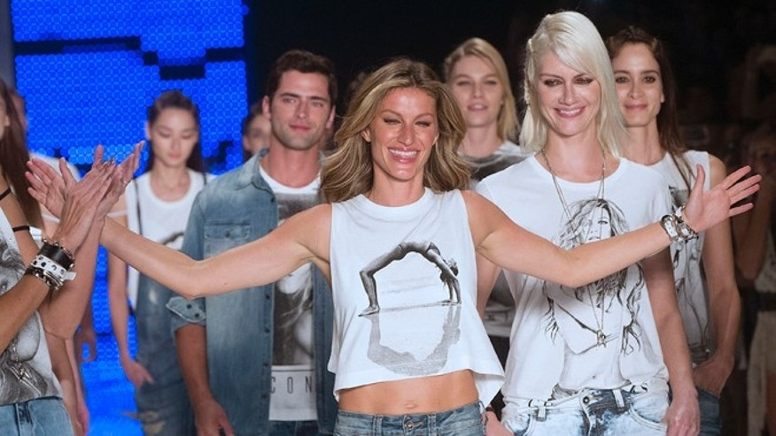 Brazilian supermodel Gisele Bundchen, center, celebrates at the end of the show from the Colcci Summer collection at Sao Paulo Fashion Week in Sao Paulo, Brazil, Wednesday, April 15, 2015. Bundchen, the Brazilian supermodel who has lit up catwalks around the world for 20 years, is retiring from the runway. (AP Photo/Andre Penner)