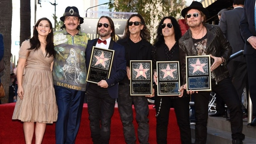 Guest speakers America Ferrera, from left, and Carlos Santana pose with Mana members, from third left, Sergio Vallin, Juan Calleros, Alex Gonzalez and Fher Olvera after the Mexican rock band received a star on the Hollywood Walk of Fame on Wednesday, Feb. 10, 2016, in Los Angeles. (Photo by Chris Pizzello/Invision/AP)