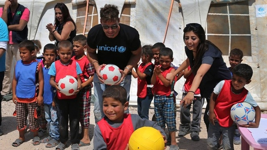 In this picture taken on Thursday June 2, 2016, Ricky Martin, center, the world-renowned singer and UNICEF goodwill ambassador, holds a ball as he plays with Syrian children, during his visit to an informal Syrian refugee camp, in Minnieh, near the northern city of Tripoli, Lebanon.(AP Photo/Hussein Malla)