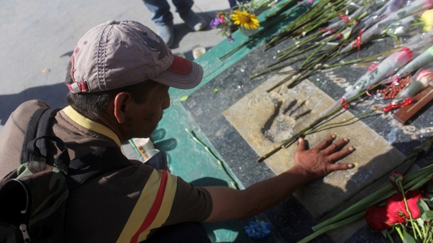 A man places his hand on a plaque with the hand prints of Mexican singer and songwriter Juan Gabriel at the site where the Noa Noa once stood, the once famous nightclub where Juan Gabriel started his singing career, in the Mexican northern border city of Ciudad Juarez, Mexico, Monday Aug. 29, 2016. Juan Gabriel, who went on to become a superstar and an icon in the Latin music world, died Sunday at his home in California at age 66, his publicist said. (AP Photo/Raymundo Ruiz)