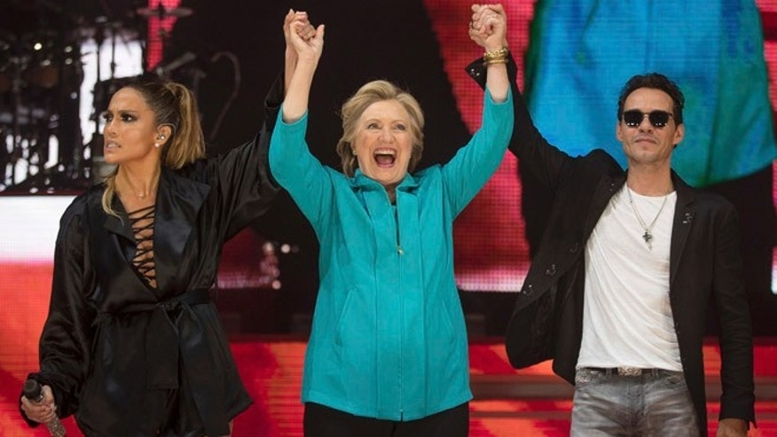 Democratic presidential candidate Hillary Clinton, center, stands with performer Jennifer Lopez, left, and singer-songwriter Marc Anthony, right, at a Get Out The Vote performance at Bayfront Park Amphitheater in Miami, Saturday, Oct. 29, 2016. (AP Photo/Andrew Harnik)