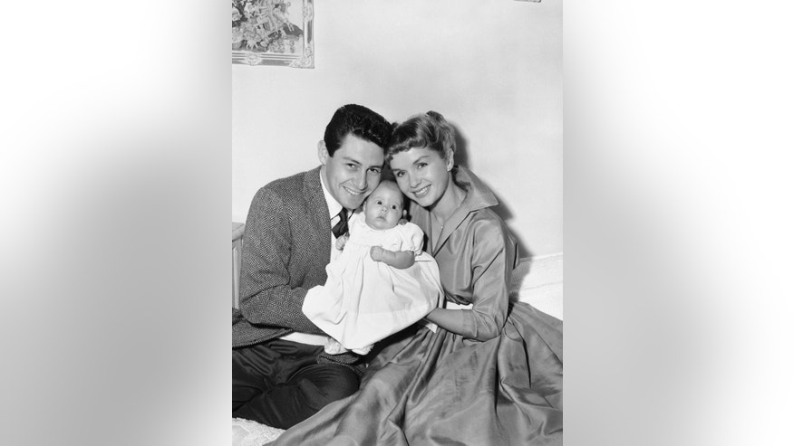 "Eddie Fisher and Debbie Reynolds appear before the camera in their real roles of happy parents as they and their young daughter, Carrie Frances Fisher, pose for their first family group picture, in Hollywood, Jan. 2, 1957.   Carrie Frances was born Oct.21, 1956.    The young stars, appropriately, are appearing in a film titled ""Bundle of Joy."" (AP Photo)"