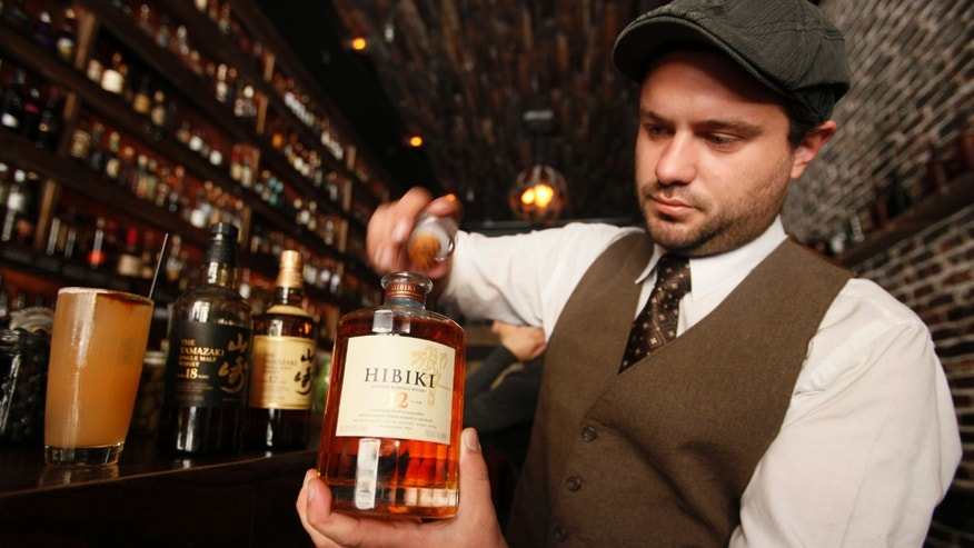 General manager Owen Westman opens a bottle of 12-year-old Hibiki Japanese whisky at the Rickhouse bar in San Francisco, Friday, Aug. 6, 2010. At left is a cocktail called the Mamie Taylor made with Japanese whiskey along with bottles of Yamazaki whiskeys.  Although best known for sake, Japan has a whisky tradition stretching back more than a century. It's not widely available in the U.S., but that's changing as companies like major producer Suntory work to boost overseas sales.(AP Photo/Eric Risberg)