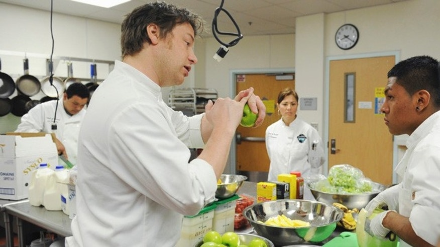 "This undated photo courtesy of ABC shows celebrity chef Jamie Oliver during a scene filmed in Los Angeles from the second season of ""Jamie Oliver's Food Revolution,"" on the ABC Television Network. The second season of ""Jamie Olivers Food Revolution,"" which begins Tuesday, April 12, started poorly when the Los Angeles school district barred Oliver's cameras _ greatly complicating a show that focuses on school lunches.     (AP Photo/ABC, Mitch Haddad)"