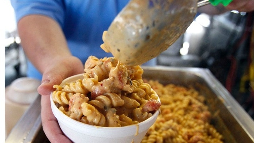 Justin Anderson scoops a helping of Crawfish Monica into a bowl before serving it at theNew Orleans Jazz and Heritage Festival in New Orleans, Sunday, May 8, 2011. Food is a popular draw at the annual festival, and vendors must try out to have the chance to sell their products. (AP Photo/Patrick Semansky)