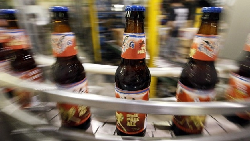 In this July 25, 2011 photo, beer bottles move along a conveyor belt after being filled at the Flying Dog Brewery in Frederick, Md. The company plans to end shipments to more than a dozen states beyond the east coast in order to burnish its image as a craft brewer and attract more consumers who are interested in buying local. (AP Photo/Patrick Semansky)