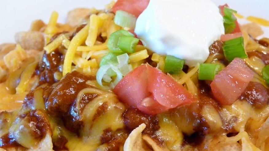 Frito Pie is made with chili, cheese, and of course Frito corn chips.