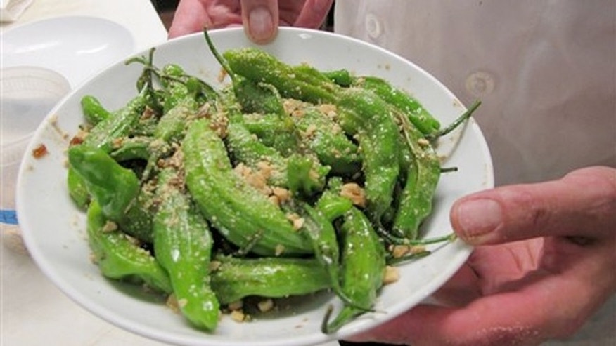 July 12, 2012:  Chef Dan Jacobs holds a plate of shishito peppers at Roots Restaurant and Cellar in Milwaukee.