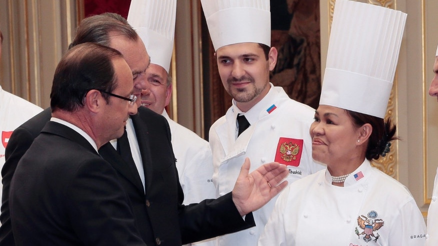 "July 24, 2012: French President Francois Hollande, left, shakes hands with Cristeta Comerford, chef at the White House, the US president official residence, as Vakhtang Abushidi, center, chef at the Kremlin in Moscow looks on during a reception at the Elysee palace in Paris, following the ""Chef des Chefs Club"" (CCC) international meeting."