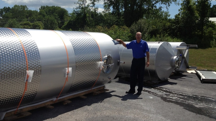 Owner Chris Jennings and the fermenting tanks he crafted to Anthony Road Winery in the Finger Lakes of New York State.