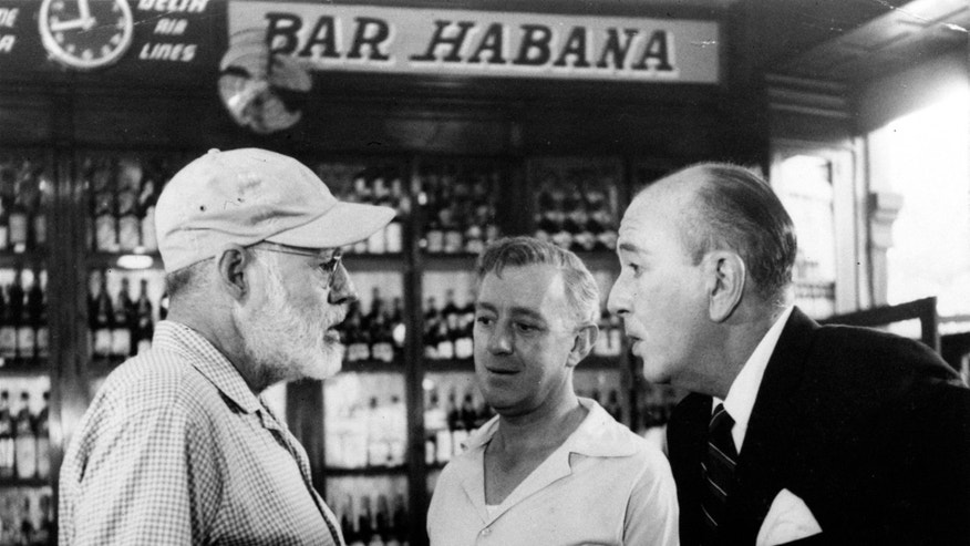 FILE - In this  May 12, 1959, American novelist Ernest Hemingway, left, speaks with actors Alec Guinness, center, and Noel Coward in Sloppy Joe's Bar.