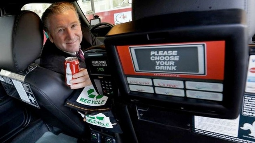 Simon Garber, owner of New Orleans Carriage Cab, poses inside a taxi cab with a backseat vending machine in New Orleans.