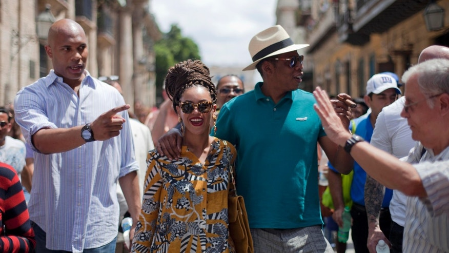 April 4, 2013: U.S. singer Beyonce and her husband, rapper Jay-Z, right, tours Old Havana as a body guard, left, and tour guide, right, accompany them in Cuba. R&B's power couple is in Havana on their fifth wedding anniversary.