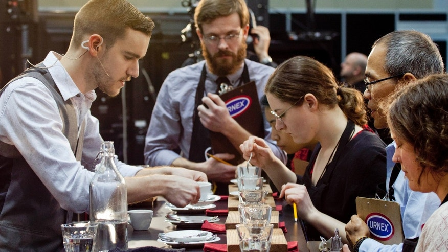 Barista competitor Nick Purvis, left, of Santa Barbara, Calif., presents one of his brewed entries to a panel of judges at the annual United States Barista Championship in Boston.