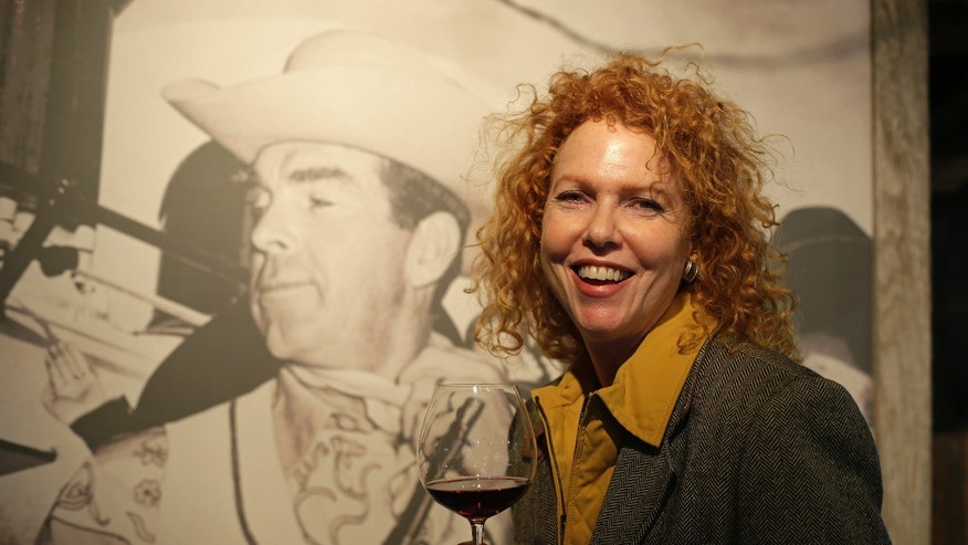 March 15, 2013: Kate MacMurray, daughter of the late actor Fred MacMurray poses with a glass of Pinot Noir by a photograph of her father in a tasting area and gallery of old photographs at the MacMurray Ranch in Healdsburg, Calif.