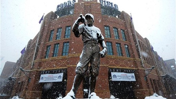 A statue of Branch Rickey is covered in snow outside of Coors Field before a baseball game between the New York Mets and the Colorado Rockies, Monday, April 15, 2013, in Denver. The game has been postponed by a heavy spring snowstorm. The teams will play a split-doubleheader Tuesday. (AP Photo/Jack Dempsey)