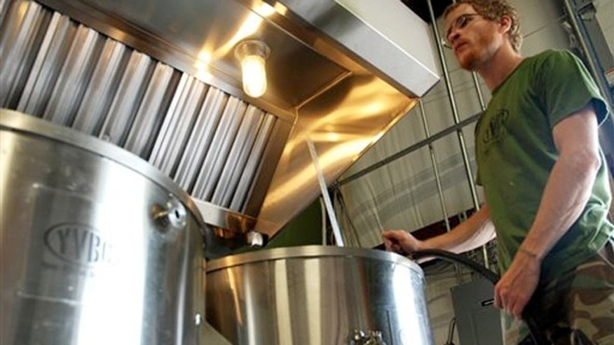 "Aug. 14, 2013:  Neil McCanon, Iraq War veteran and head brewer at Young Veterans Brewing Co., adds water to the brew kettle as he prepares to brew ""Pineapple Grenade Hefeweizen."""
