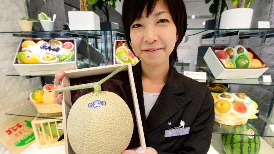 Miyuki Kaida, employee of Japan's fruit shop chain 'Sun Fruits', shows off their high quality produce in Tokyo on September 17, 2013
