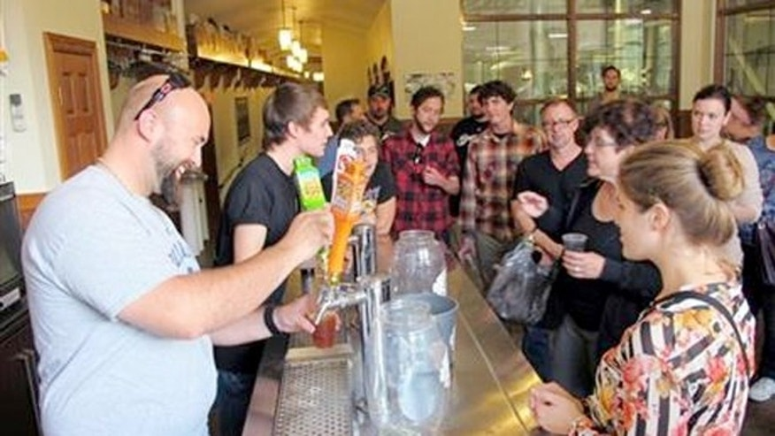 Oct. 3, 2013:  \Mark Paprocki, left, and Dylan Maz pour beer during a tour at Lakefront Brewery in Milwaukee.