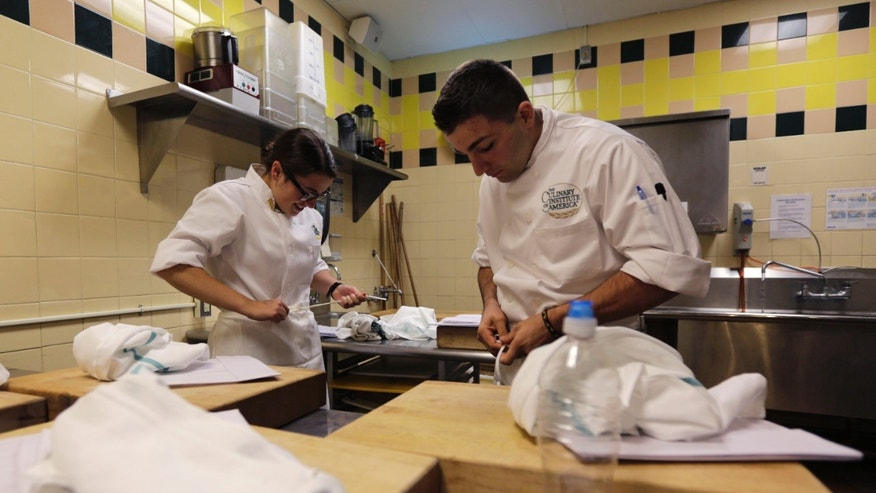 Oct. 16, 2013: West Point Cadet Calla Glavin of Birmingham, Mich., left, and Culinary Institute of America student Andrew Worgul of Vernon, N.J., tie their aprons before cooking.