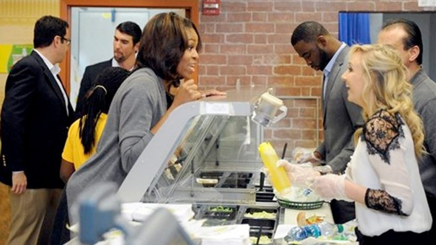January 23, 2014: Famous Fans Justin Tuck, second from right, and Nastia Liukin, right, work behind the counter to serve up Fresh Fit sandwiches to First Lady Michelle Obama.