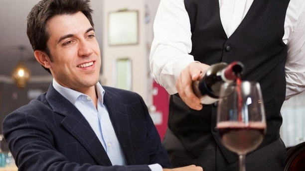 Waiter pouring wine to a customer