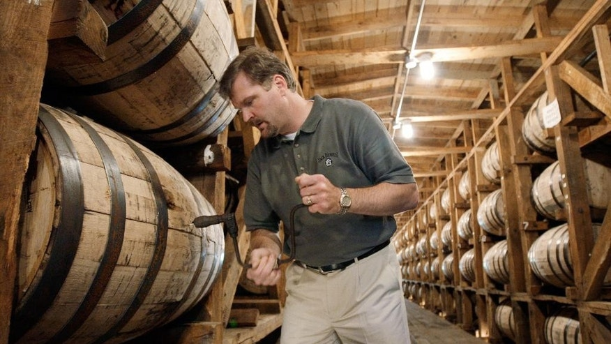 FILE: Jeff Arnett, the master distiller at the Jack Daniel Distillery in Lynchburg, Tenn., drills a hole in a barrel of whiskey in one of the aging houses at the distillery.