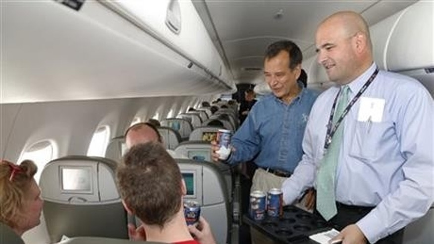 Jim Koch, founder and brewer of Samuel Adams, left, and Marty St. George, SVP of Marketing and Commercial at JetBlue hand out Boston Lager cans on the inaugural JetBlue flight from Boston to New York.
