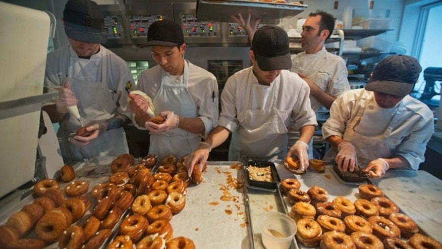 June 3, 2013: In this file photo, a baking crew makes Cronuts, a croissant-donut hybrid, at the Dominique Ansel Bakery in New York.