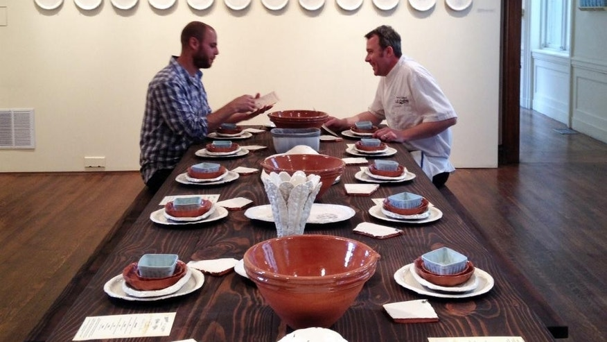 "Artist Gregg Moore, left, and chef  Pierre Calmels at a table set with Moore's fine ceramic pottery for a show called ""Heirloom,""  in Philadelphia."