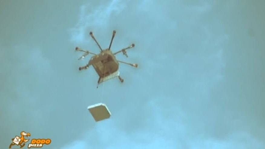 The drone lowers pizza to hungry onlookers by cable.