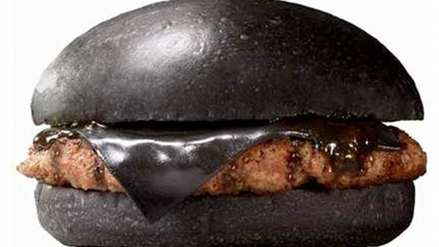 The Kuro Peral Burger is layered with black cheese, a beef patty on a black bun made with bamboo charcoal, and a sauce made with onion and squid ink.