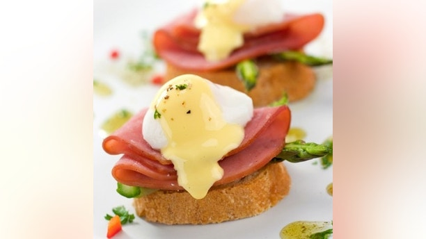 Two delicious eggs benedict with asparagus and garnish.  Shallow dof.