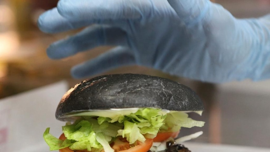 "FILE - In this Sept. 16, 2014 file photo, Burger King's new menu Kuro Diamond burger is prepared by employee Rumi Sekine at its Shibuya restaurant in Tokyo. The fast-food chain is offering customers an initially unappetizing experience as it launched two limited edition ""Kuro"" burgers with black buns, black sauce and black cheese on Friday. Kuro means black in Japanese. (AP Photo/Koji Sasahara, File)"