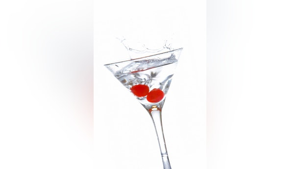 Two red cherrys splashing into a cocktail glass