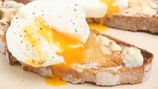Poached eggs on buttered toast from a rustic white bread loaf.
