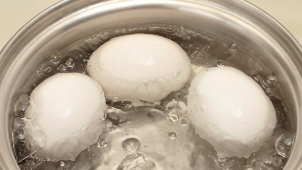 Closeup of three eggs boiling in pot of hot water