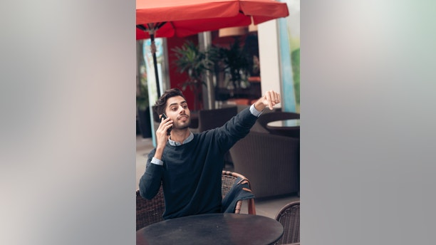 Handsome man talking on the phone and asking for waiter