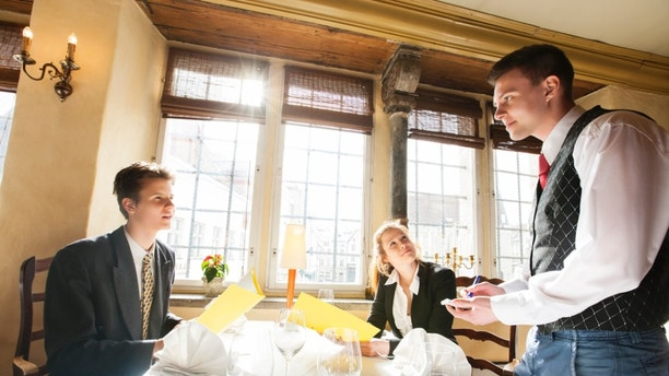 Business couple ordering food at restaurant table