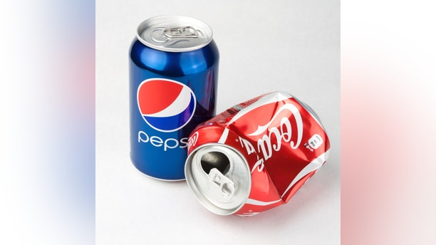 VILNIUS, LITHUANIA – OCTOBER 21, 2011: Photo of a Coca-Cola and Pepsi classic 330 ml cans. Concept of  competitiveness as Coca-Cola can is lying empty and crashed while Pepsi is still full and standing.