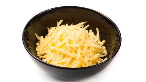 Grated cheddar cheese in a black bowl, isolated on white.