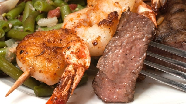 Closeup of sirloin steak on fork with shrimp on skewer and green beans.