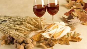 Red wine in an autumn decor with leaves, corncobs and walnuts
